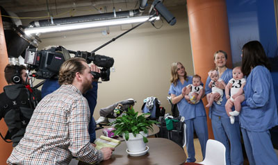 Nurses with babies being filmed