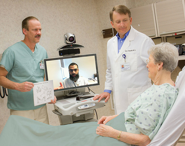 TeleStroke web team at CentraCare speaking with a patient in a hospital bed