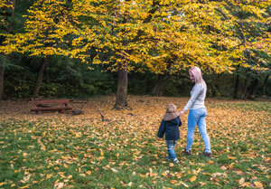 Mom playing with child in leaves