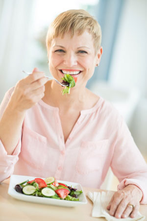 Woman with short blonde hair eating a plate of vegetables.
