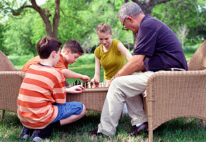 older person playing chess with kids