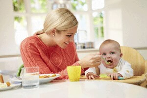Young woman with blonde hair spoon feeding a baby at a table.
