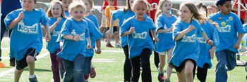 Group of children in matching shirts running on a field.