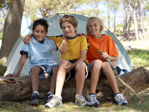 Three young kids sitting on a log in front of a tent.