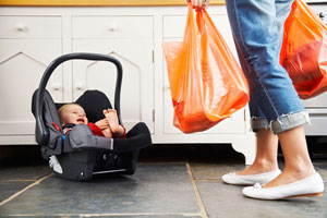 Woman carrying grocery bags with a baby sitting in a carrier on the ground by the woman's feet.