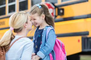 Mom saying bye to daughter at school bus