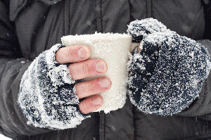Gloved, snow covered hands holding a white coffee cup.
