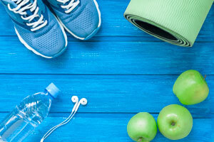 water bottle, workout shoes, apples, and yoga mat