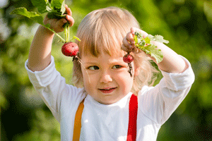 child with fresh picked radishes