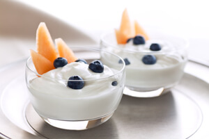 Two bowls of yogurt with fruit inside.