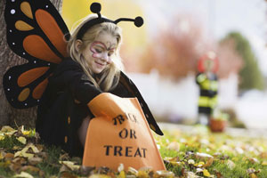 Young blonde girl wearing a butterfly costume looking in her Trick or Treat bag.