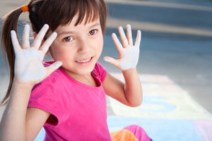 Little girl with chalk on hands