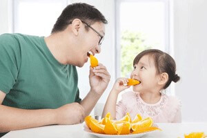 Male with dark hair and glasses eating orange with a young girl with dark hair.