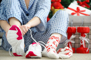 person putting sneakers on near christmas presents