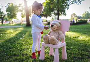 Little girl giving shot to teddy bear