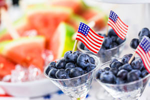 Three small bowls of blueberries with American flags in them and a bowl of watermelon in the background.