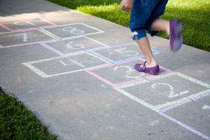 Girl hoping on one leg on pavement with chalk drawing.