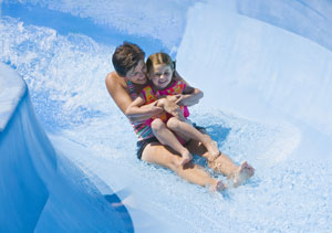Young girl held by woman coming down a water slide.