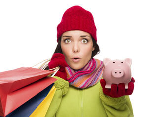 Woman wearing a red beanie and scarf holding bags in one hand and a piggy bank in the other.