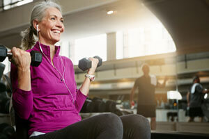 older woman lifting dumbbells at gym
