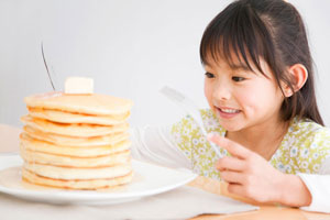 Young girl with dark hair holding a fork and knife looking at a large stack of pancakes.