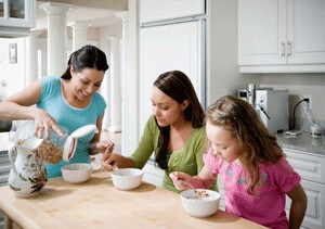 Three females sitting in the kitchen eating cereal out of white bowls.