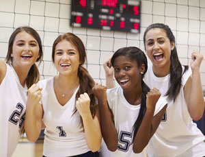 Group of young women in white jerseys in front of a volleyball net.