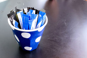 Small cup with different types of sugar packets in it.