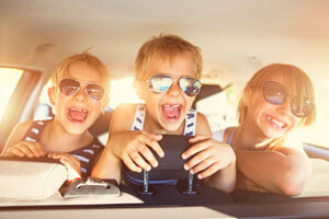 kids with sunglasses on in back of car