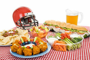 Table set with different foods, pitcher and football helmet.
