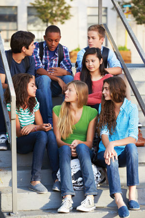 Group of teenagers sitting on steps outside.
