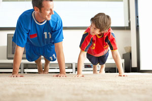 Man and boy doing a plank in a room, both wearing jerseys.