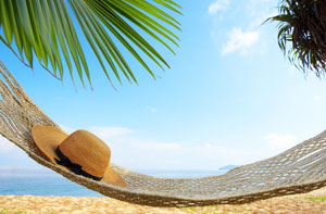 Beach scene with a hammock with a hat set on it.