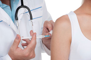 Medical provider injecting patient with syringe in upper arm