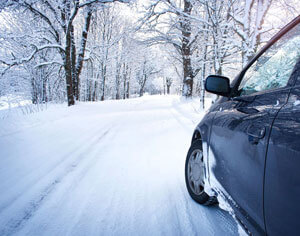 Dark colored vehicle on a snow covered road with trees.