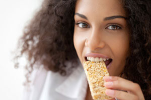 Young woman with dark hair eating a bar.