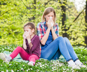 Young girl and woman sitting on grass blowing their nose.