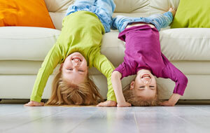 Two children hanging upside down off a couch.