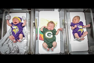 baby in greenbay packers jersey in between two babies with minnesota vikings jerseys on