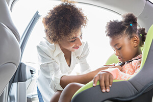 Mom strapping little girl into car seat