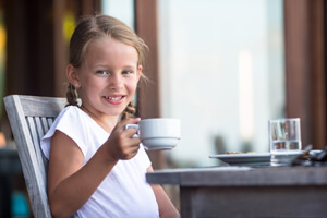 Young girl holding a coffee cup.