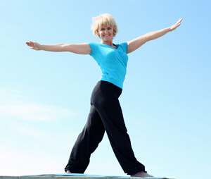 Woman in a blue shirt and black pants stretching out her arms.