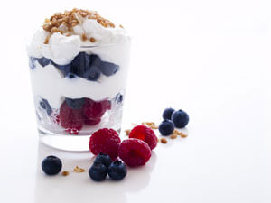 Clear cup of yogurt with fruit and granola.