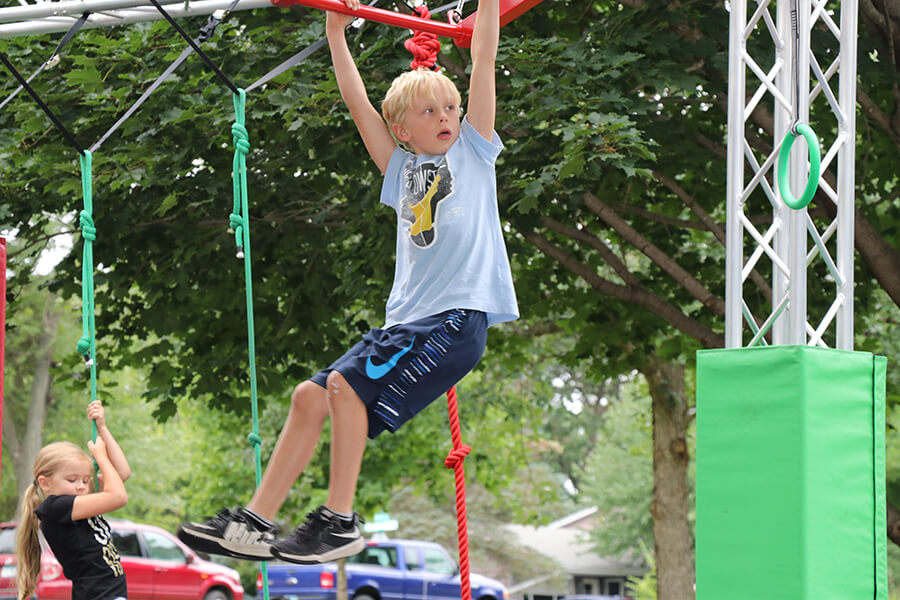 young blond child handing from the playground monkey bars