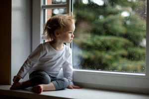 Young child sitting on a nook looking out the window.