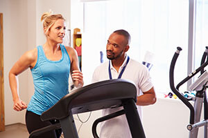 woman running on treadmill with coach next to her
