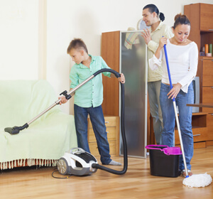 Family of three cleaning their house including mopping and vacuuming.