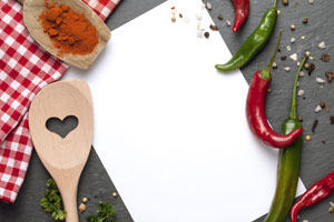 Dark grey counter top with white paper with peppers, spice and a heart cut-out spoon.