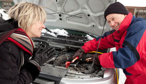 Man and woman working on a car engine.